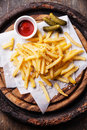 French fries with ketchup salted and pickled cucumbers on wooden background Stock Images