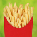 French fries in a red box over green background Stock Photo