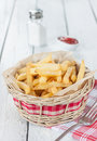 French fries in a wicker basket on white table bar or fast food menu wood with salt shaker and ketchup rural Royalty Free Stock Photo
