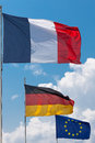 French german and european union flags flying in the wind under a sun filled sky with towering cumulus clouds in the background Royalty Free Stock Image