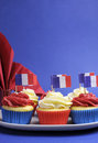 French theme red white and blue mini cupcake cakes with flags of france vertical fleur de lis napkin for national holidays Stock Images