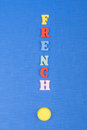 FRENCH word on blue background composed from colorful abc alphabet block wooden letters, copy space for ad text. Learning Royalty Free Stock Photo