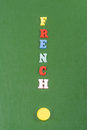 FRENCH word on green background composed from colorful abc alphabet block wooden letters, copy space for ad text Royalty Free Stock Photo