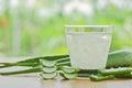 fresh aloe vera leaves and aloe vera juice in glass on wooden ba