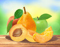 Fresh apricot, peach, apple and pear on wooden plate over nature Royalty Free Stock Photo