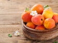 Fresh apricots in wooden bowl selective focus Stock Images