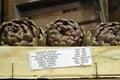 3 fresh artichokes green-purple flower head, on wooden backgroun Royalty Free Stock Photo