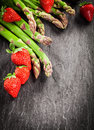 Fresh asparagus spears and ripe red strawberries uncooked green arranged as a corner decoration on textured grey slate with Royalty Free Stock Photography