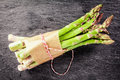 Fresh asparagus spears tied with brown paper bundle of farm green and string on a dark textured slate background overhead view Stock Photo