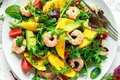 Fresh Avocado, Shrimps, Mango salad with lettuce green mix, cherry tomatoes, herbs and olive oil, lemon dressing Royalty Free Stock Photo