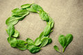 Fresh Baby spinach leaves on sackcloth background. Top view with copy space, round circle frame. Love, Healthy, Ecology