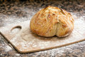 Fresh baked artisan bread freshly on a marble background and cutting board with flour Stock Photo