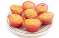 Fresh baked carrot muffins in red silicone cups closeup of muffin with and cinnamon on colorful plate isolated on white background Royalty Free Stock Photography