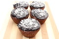 Fresh baked chocolate muffin with desiccated coconut on chopping board closeup of cacao and white background Stock Photo