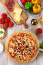 Fresh baked supreme pizza on wooden board and table, with colorful veggie ingredients, vertical overhead top view Royalty Free Stock Photo