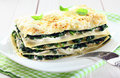 Fresh baked vegetarian spinach lasagna on a plate close up of with fork and over napkin and an old white wooden table Stock Image