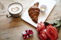 Fresh bakery croissant, coffee with heart sign, rose flowers on wooden table. Romantic breakfast for Valentine`s Day celebrate con Royalty Free Stock Photo