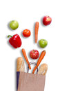 Fresh balanced grocery shopping concept with a brown paper carrier bag with crusty baguette carrots apples sweet bell pepper Stock Photography