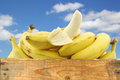 Fresh bananas and a peeled one in wooden crate against blue sky with clouds on white background Royalty Free Stock Image
