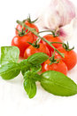 Fresh basil and cherry tomatoes garlic on a wooden background Royalty Free Stock Images