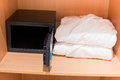 Fresh bathrobes and open safe at closet shelf scene in hotel room prepared Stock Photos