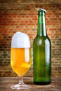 Fresh beer with foam frosty in a glass and in a bottle rustic background Stock Photos