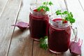 Fresh beet juice in mason jars with beets over rustic wood Royalty Free Stock Photo