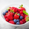 Fresh berries, blueberry, strawberry, raspberry with mint leaves in a white ceramic bowl on a gray stone background Royalty Free Stock Photo