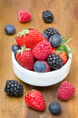 Fresh berries in a bowl on a wooden background strawberries raspberries blackberries blueberries Stock Image