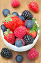 Fresh berries in a bowl on a wooden background strawberries raspberries blackberries blueberries closeup Royalty Free Stock Photos