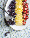 Fresh berries and fruits on plate pineapple grapes strawberry Royalty Free Stock Photography