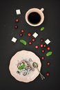 Fresh berries on tart cake cup coffee fresh cranberry and sugar cubes over black background top view Royalty Free Stock Photos