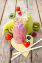 Fresh blended fruit smoothies in vintage milk bottles with berries on rustic wooden table Stock Photo