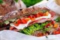 Fresh BLT Sandwich with Bacon Lettuce Tomato and Mozzarella on crumpled paper Royalty Free Stock Photo