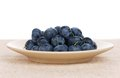 Fresh blueberries on a plate on a sac over white background Royalty Free Stock Images