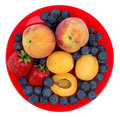Fresh blueberry, strawberry, peach and apricot on a red plate Royalty Free Stock Photo