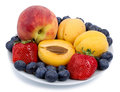 Fresh blueberry, strawberry, peach and apricot on a white plate Royalty Free Stock Photo