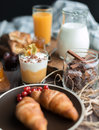 Fresh brakfast two croissants on brown plate and cream mousse in the little glass and spices in jar on the wooden table Royalty Free Stock Images