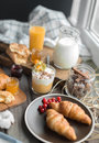 Fresh brakfast two croissants on brown plate and cream mousse in the little glass and spices in jar on the wooden table Royalty Free Stock Photos