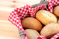 Fresh bread rolls in a rustic picnic basket detail of lined with red gingham Stock Photography