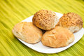 Fresh bread rolls with sunflower and sesame seeds on white plate table set Stock Photos