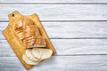Fresh bread slices on cutting board against white grey wooden background. Top view Royalty Free Stock Photo