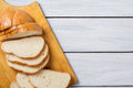 Fresh bread slices on cutting board against white wooden background. Top view Royalty Free Stock Photo