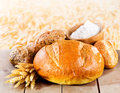Fresh bread with wheat ears on wooden table Stock Images