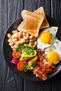 Fresh breakfast: fried eggs with bacon, beans, toast and vegetab Royalty Free Stock Photo