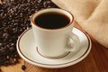 Fresh brewed coffee a cup of with dark roasted beans in the background Royalty Free Stock Images