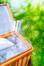 Fresh bright picnic basket with a blue and white checked country lining open to display glasses and cups against lush greenery Stock Images