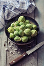 Fresh brussels sprout in bowl on wooden background Stock Photos