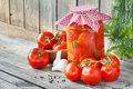 Fresh and canned tomatoes homemade preserves in glass jar on wooden board Stock Photo
