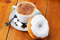 Fresh cappuccino and doughnut with white frosting cup of hot coffee next to donut Stock Images